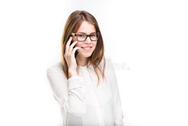 La belle jeune fille dans une chemise blanche sur le blanc a isolé le fond parlant à un téléphone portable Sourit le portrait au photographie stock