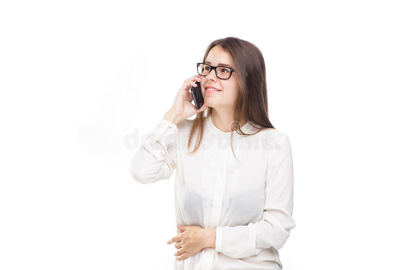 La belle jeune fille dans une chemise blanche sur le blanc a isolé le fond parlant à un téléphone portable Sourit le portrait à l photo libre de droits