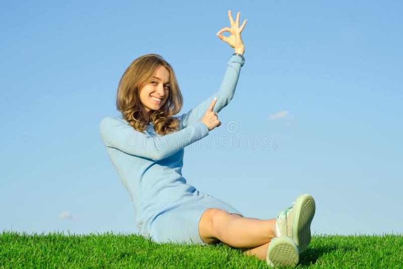 La belle jeune fille dans une robe s'assied sur l'herbe photo libre de droits