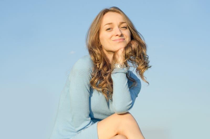 La belle jeune fille dans une robe s'assied sur un fond de ciel photo libre de droits