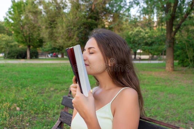 La belle jeune fille de brownhair sent un livre imprimé frais se reposant sur le banc en parc photo libre de droits