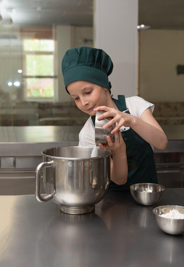 La belle jeune fille de chef de cuisinier dans le chapeau vert de chef verse le sucre dans une grande cuvette image libre de droits
