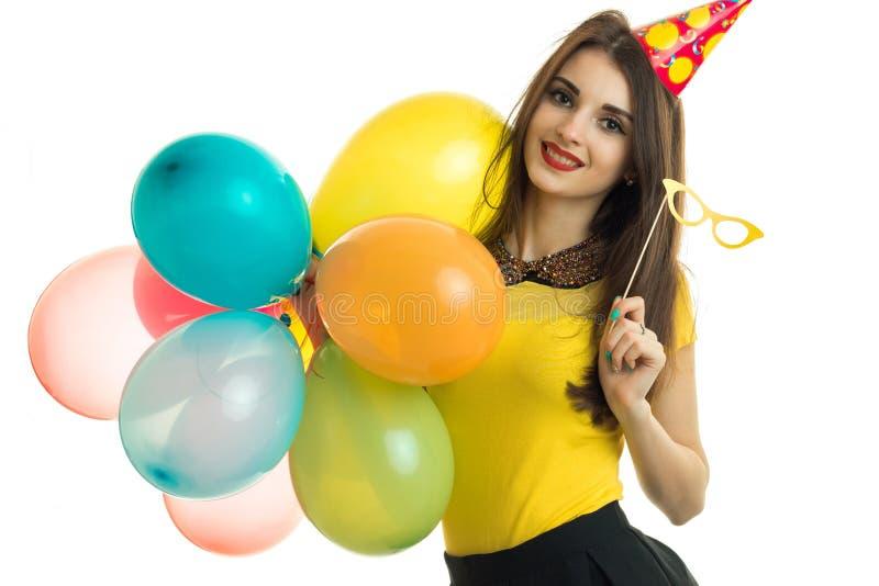 La belle jeune fille de sourire avec le rouge à lèvres rouge maintient beaucoup de ballons et verres disponibles photographie stock libre de droits