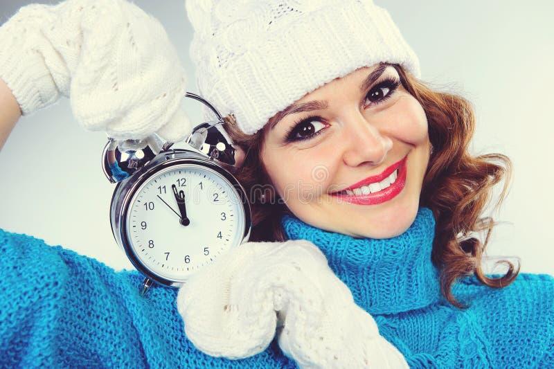 La belle jeune fille en hiver vêtx avec le réveil photos stock