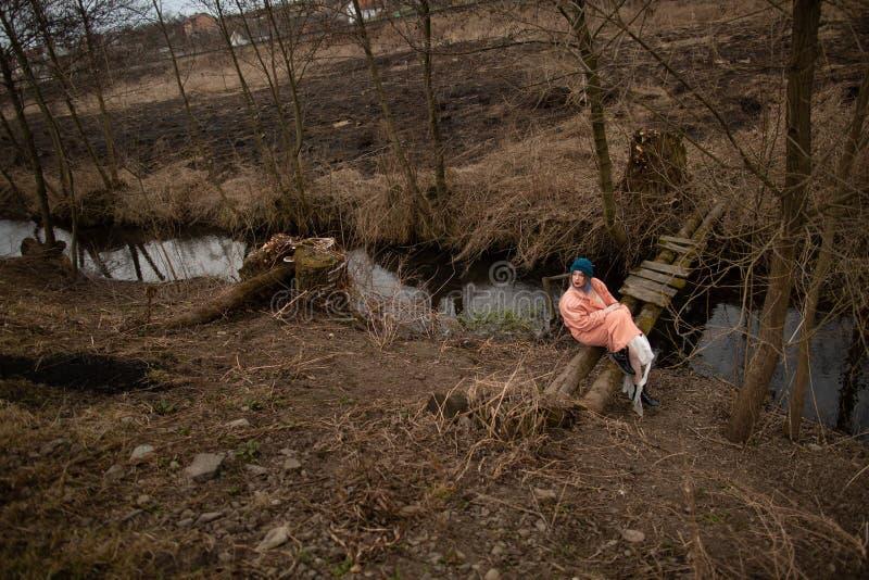 La belle jeune fille est repos, se reposant sur un petit pont en bois photos stock