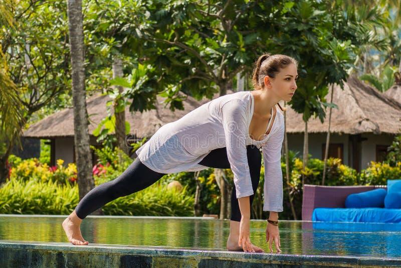 La belle jeune fille fait la pratique en matière de yoga, étirant des jambes sur la piscine avec les plantes vertes et les palmie images stock