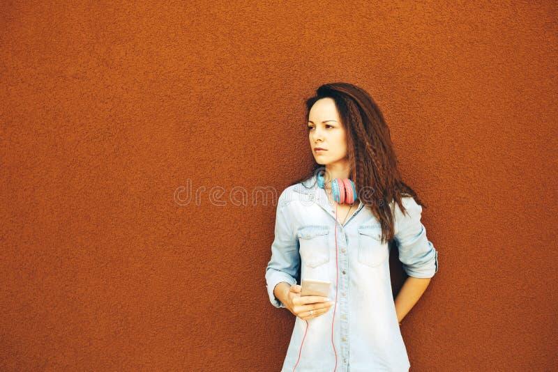 La belle jeune fille moderne dans des écouteurs avec un téléphone se tient près du mur orange Le concept du style, de la jeunesse images stock