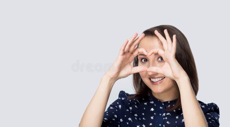 La belle jeune fille montre l'émotion sur un fond rose photo stock