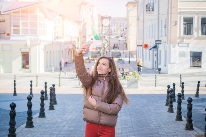 La belle jeune fille prend des photos d'elle-même sur une rue de ville images libres de droits