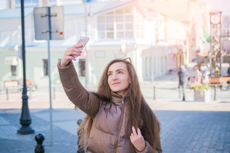 La belle jeune fille prend des photos d'elle-même sur une rue de ville image libre de droits