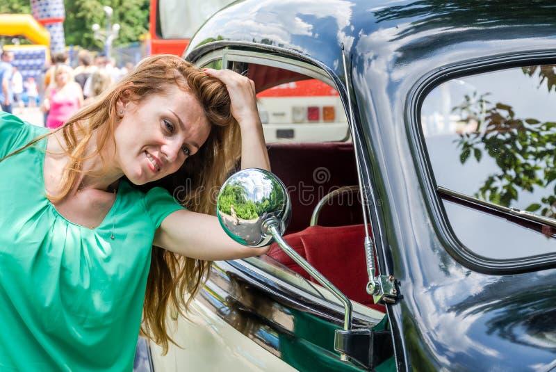 La belle jeune fille redresse ses cheveux dans le miroir d'une vieille voiture de vintage image stock