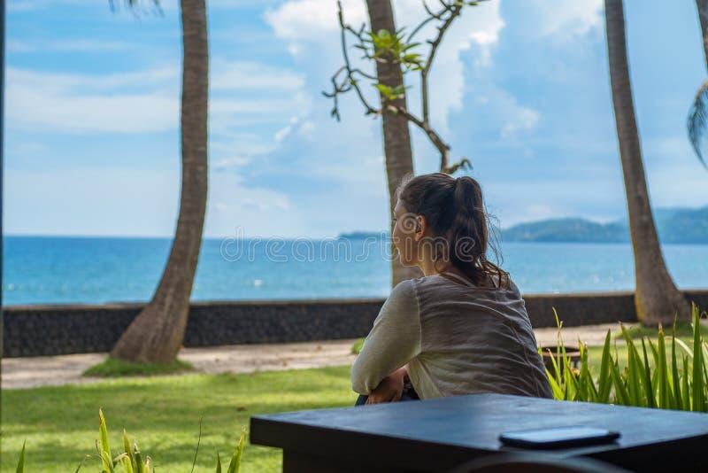 La belle jeune fille s'assied sur la véranda que le pavillon examine la distance sur la plage d'océan en île Indonésie de Bali photo libre de droits
