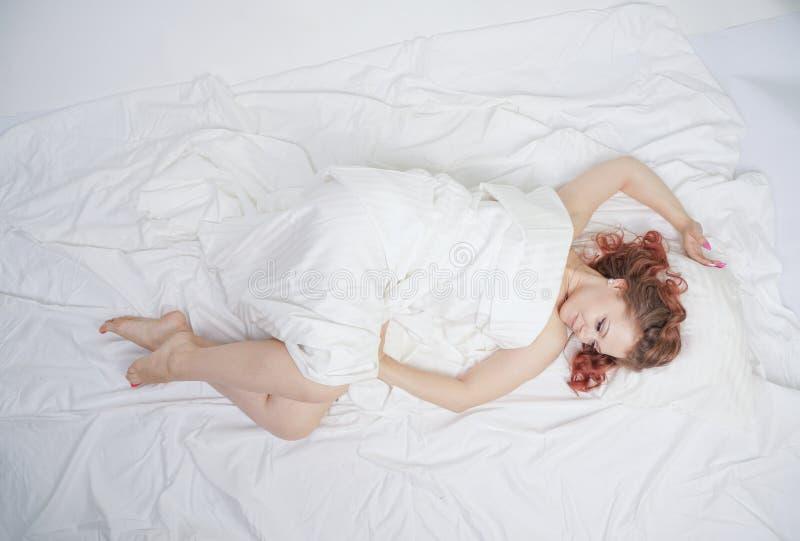La belle jeune fille se trouve sur un lit blanc et apprécie le matin la femme caucasienne de charme est heureuse et détente somno photos stock