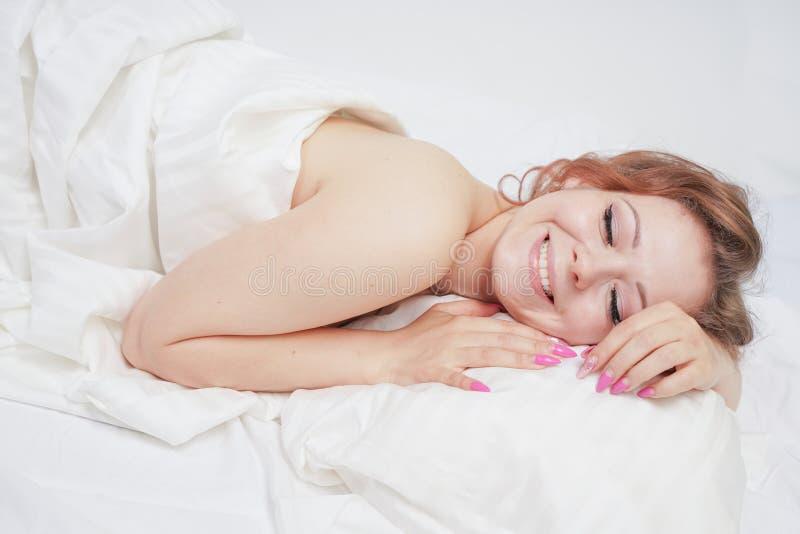 La belle jeune fille se trouve sur un lit blanc et apprécie le matin la femme caucasienne de charme est heureuse et détente somno photographie stock