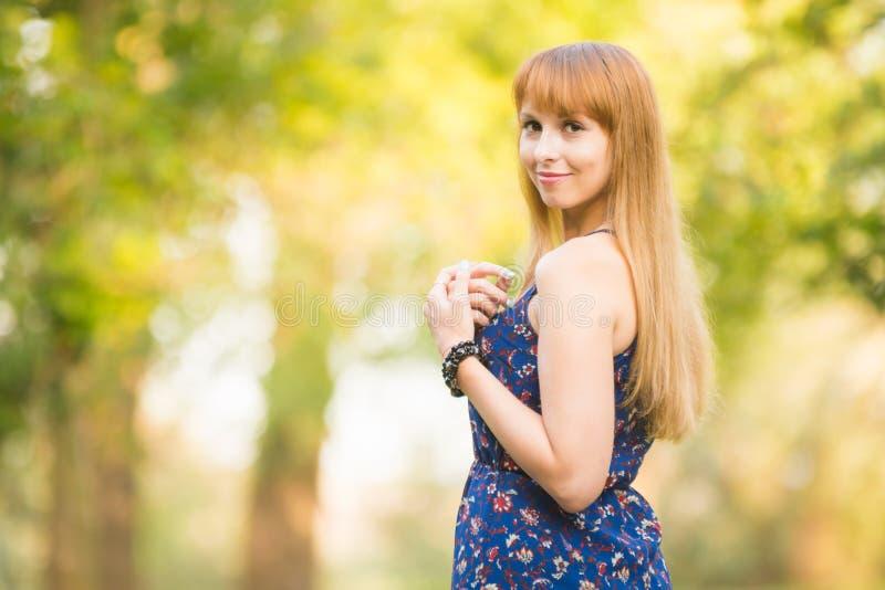 La belle jeune fille a tourné et a recherché avec un sourire dans le cadre sur le fond de la verdure brouillée ensoleillée photo libre de droits