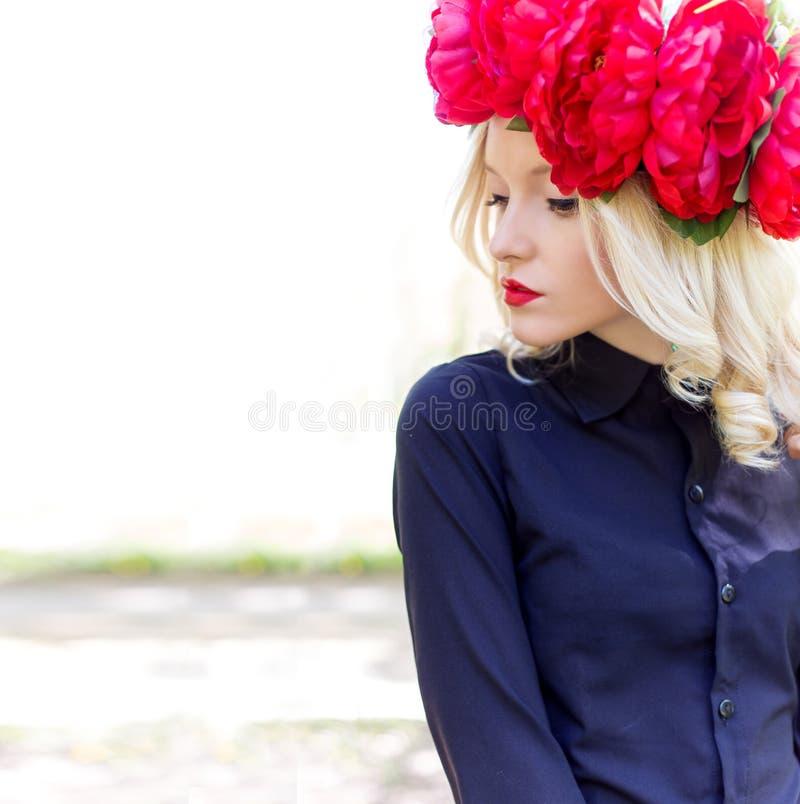 La belle jeune jeune femme blonde élégante douce avec une couronne rouge de pivoine dans un chemisier noir marche dans le champ d images stock