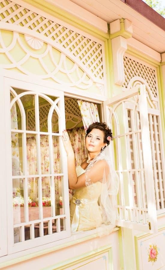 La belle jeune jeune mariée avec du charme s'assied sur image stock