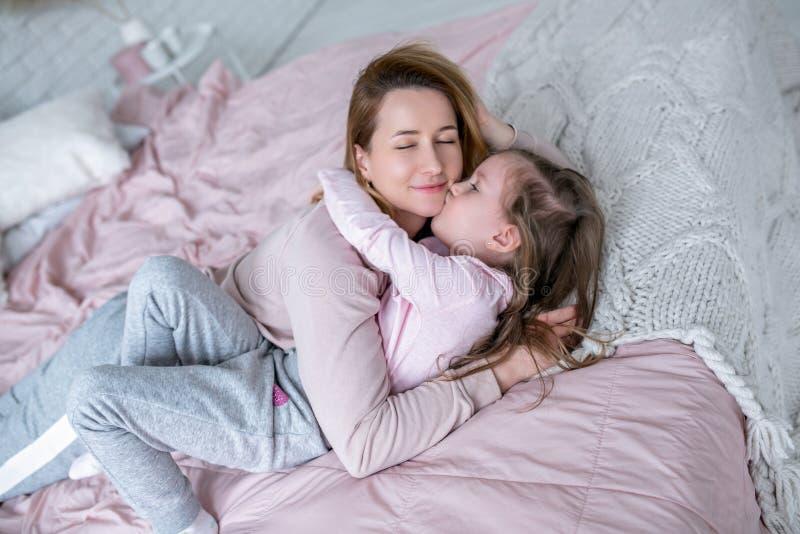 La belle jeune mère et sa petite fille se trouvent ensemble sur le lit dans la chambre à coucher, jouent, étreignent et ont l'amu image stock