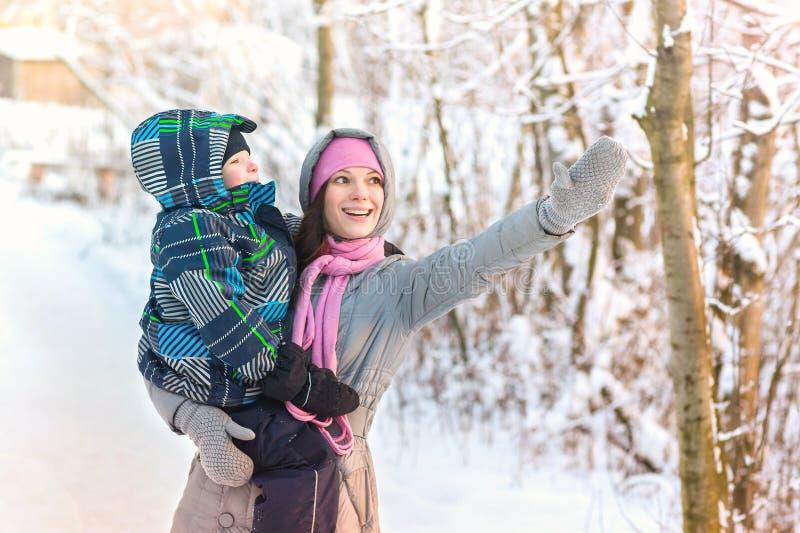La belle jeune mère marchant avec son fils dans la forêt d'hiver lui montre quelque chose dans le ciel photos stock