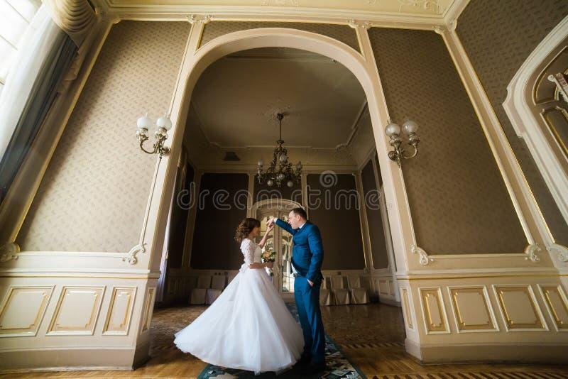 La belle jeune mariée avec le bouquet et le marié beau portant la danse bleue de costume dans la voûte au jaune mure le fond images stock