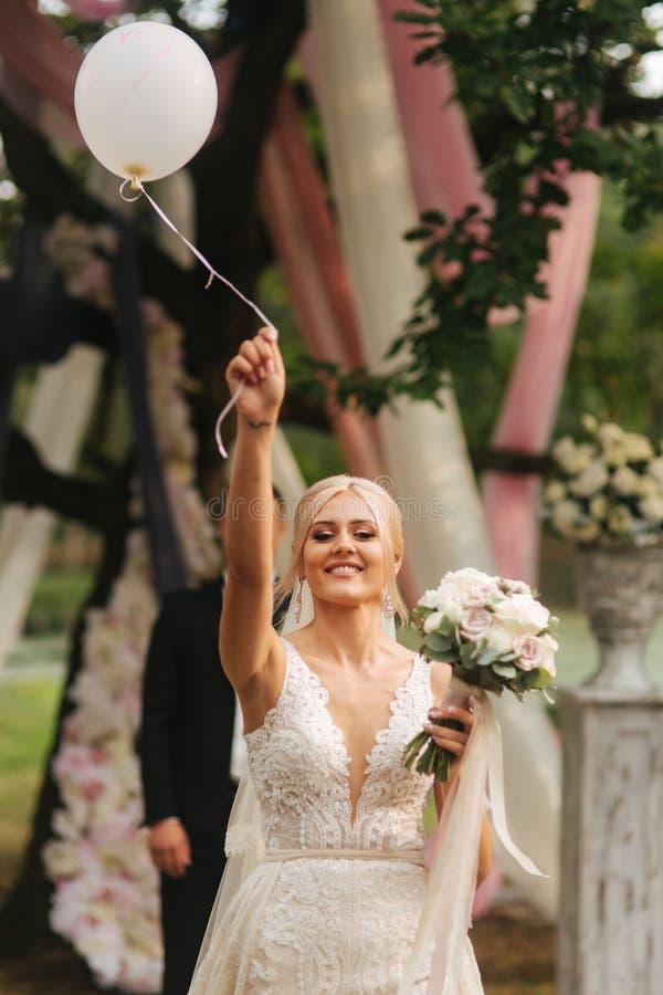 La belle jeune mariée avec le bouquet a laissé aller la boule sur la cérémonie de mariage photos stock