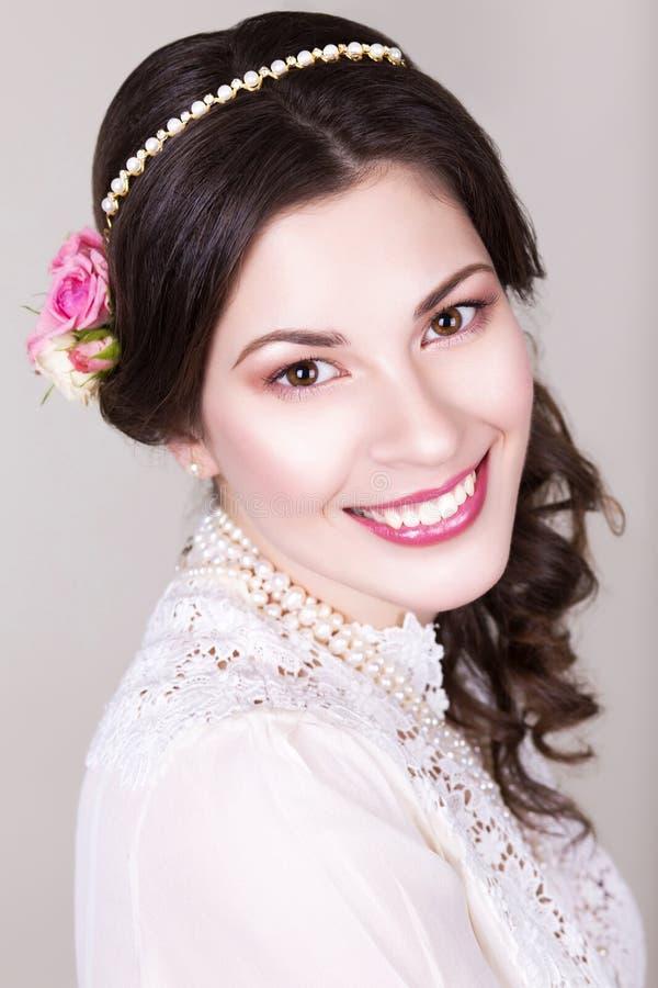 La belle jeune mariée de brune souriant avec naturel composent et fleurissent des roses dans sa coiffure photographie stock libre de droits