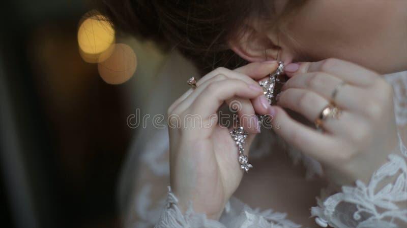 La belle jeune mariée met dedans dessus la boucle d'oreille La fille modèle de beauté porte des bijoux pour le mariage Épouser le photo libre de droits