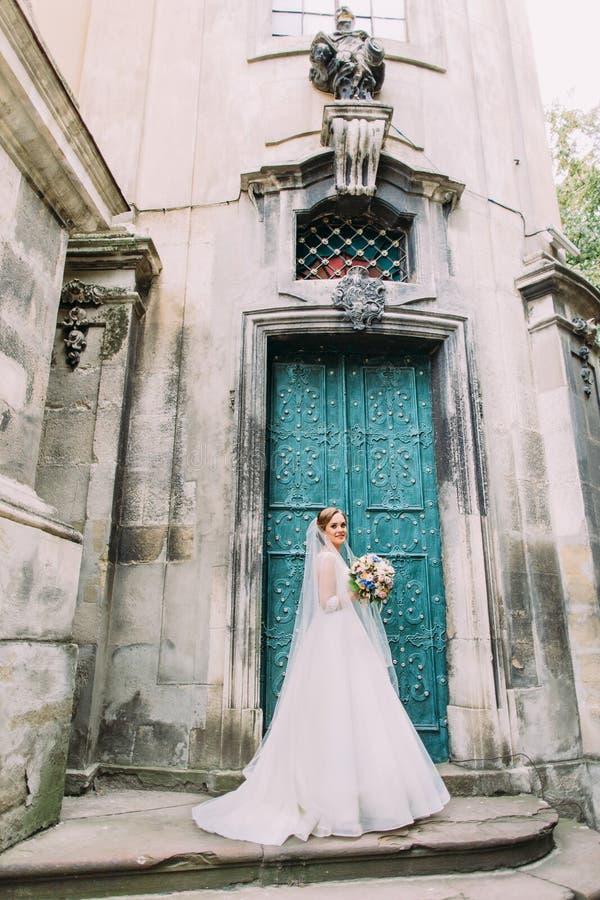La belle jeune mariée pose près du bâtiment antique photos stock