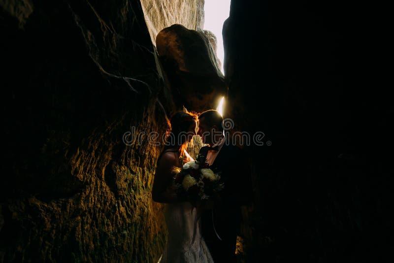 La belle jeune mariée romantique et le marié élégant élégant dans la fissure obscurcie de roche backgrounded par briller de couch image stock