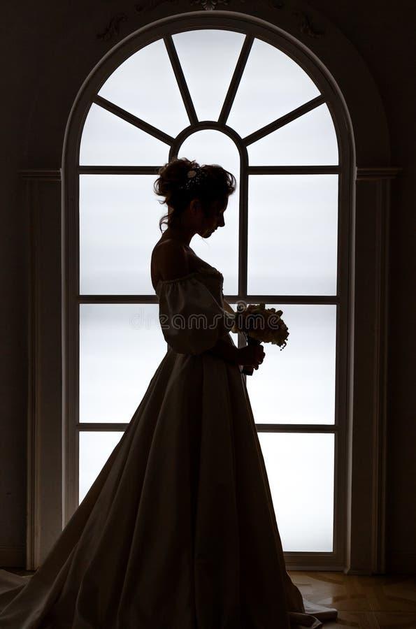 La belle jeune mariée tient la silhouette près de la fenêtre photo stock