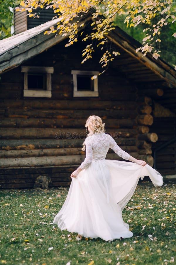 La belle jeune mariée tourne autour elle-même dans la robe de flottement sur le fond en bois de maison Vue arrière dessin-modèle photographie stock libre de droits