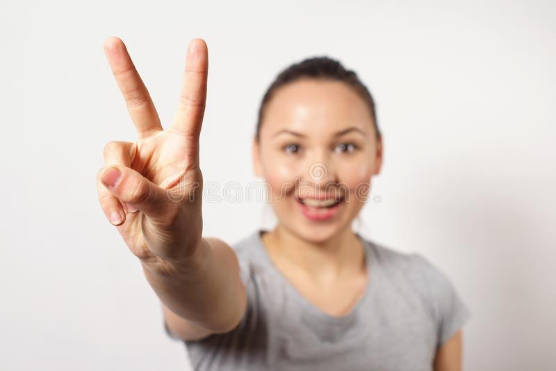 La belle jeune représentation de sourire heureuse de fille victopy chantent avec sa main Concept de paix Signe des gestes photographie stock libre de droits