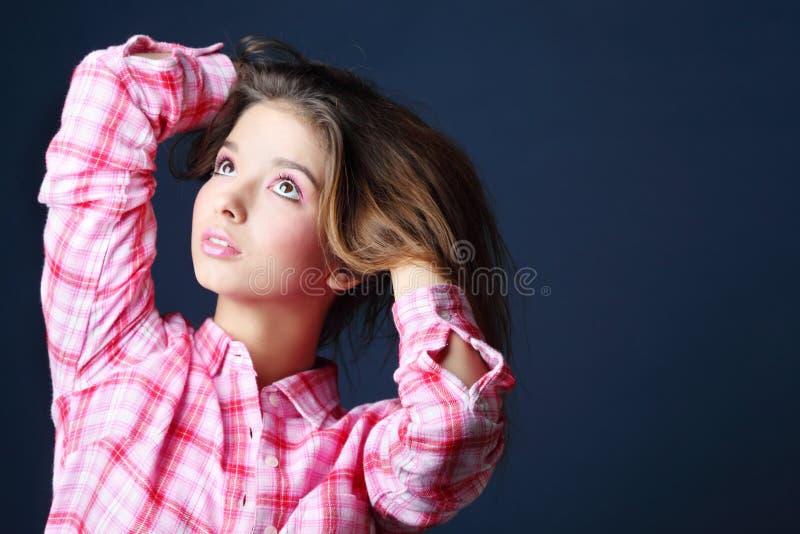 La belle jolie fille retient le cheveu et recherche image stock