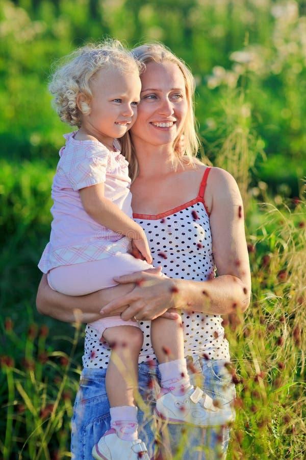 La belle mère avec l'enfant en bas âge bouclé-a dirigé le descendant photographie stock libre de droits