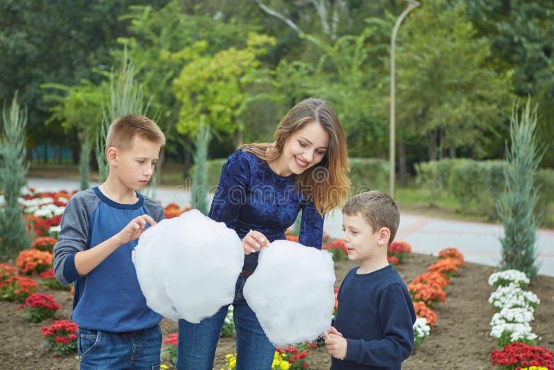 La belle mère heureuse et deux fils mangent la sucrerie de coton image stock