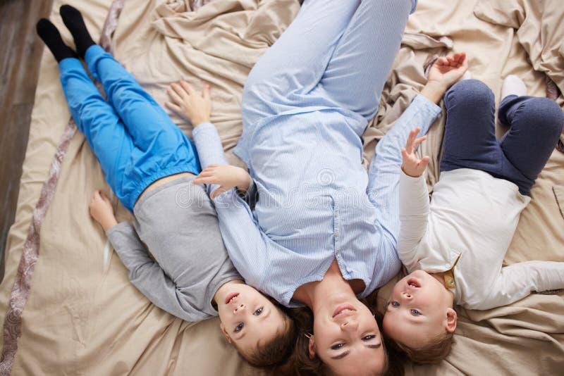 La belle mère heureuse habillée dans le pyjama bleu-clair s'étend avec ses deux peu de fils sur le lit avec la couverture beige d photo stock