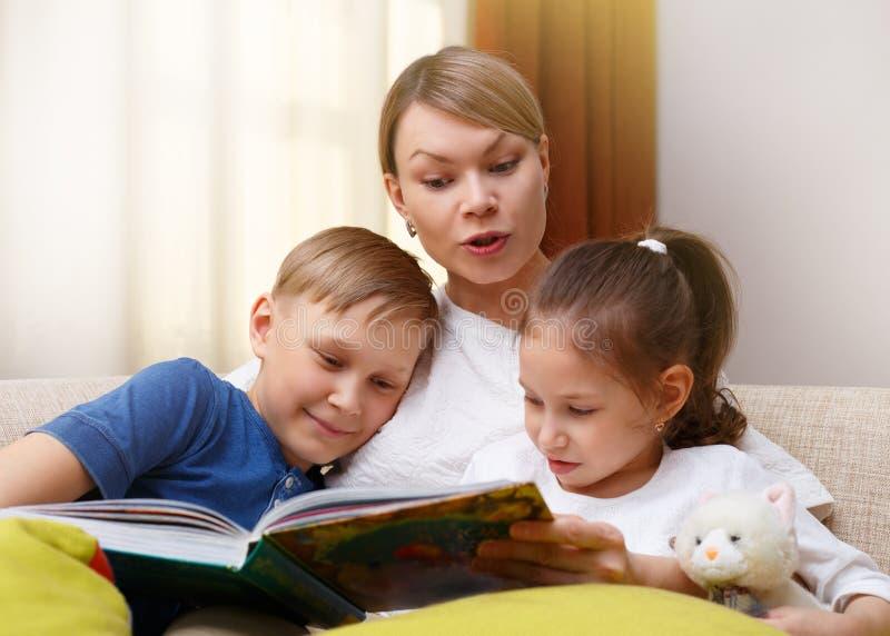 La belle mère lit un livre à ses enfants en bas âge La soeur et le frère écoute une histoire photographie stock