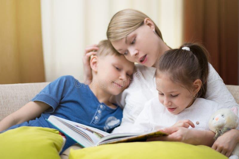 La belle mère lit un livre à ses enfants en bas âge La soeur et le frère écoute une histoire image stock