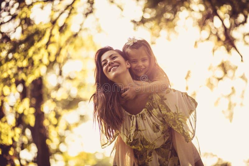 La belle mère portant sa fille ferroutent dessus images stock