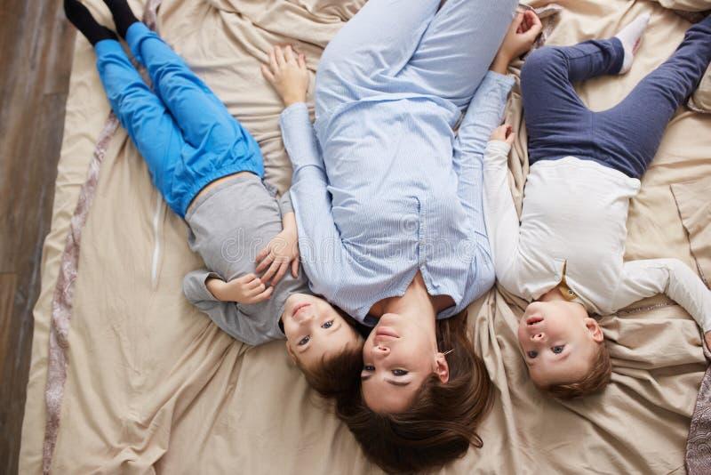 La belle m?re heureuse habill?e dans le pyjama bleu-clair s'?tend avec ses deux peu de fils sur le lit avec la couverture beige d photo libre de droits