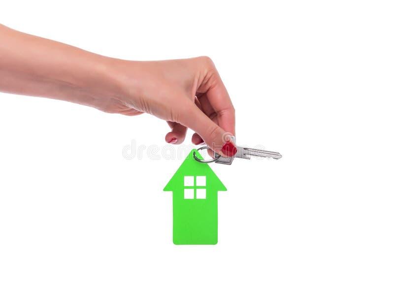 La belle main femelle tient une clé avec un keychain sous forme de maison Sur un blanc image libre de droits
