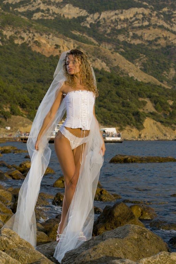 La belle mariée dans un corset est sur la roche photos libres de droits