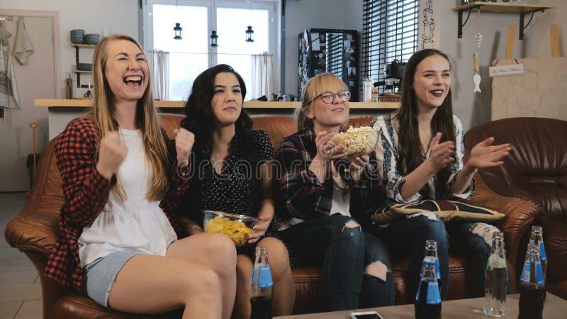 La belle montre TV d'amies, célèbrent le succès Les filles assez émotives de jeunes rient le mouvement lent de observation des sp image libre de droits