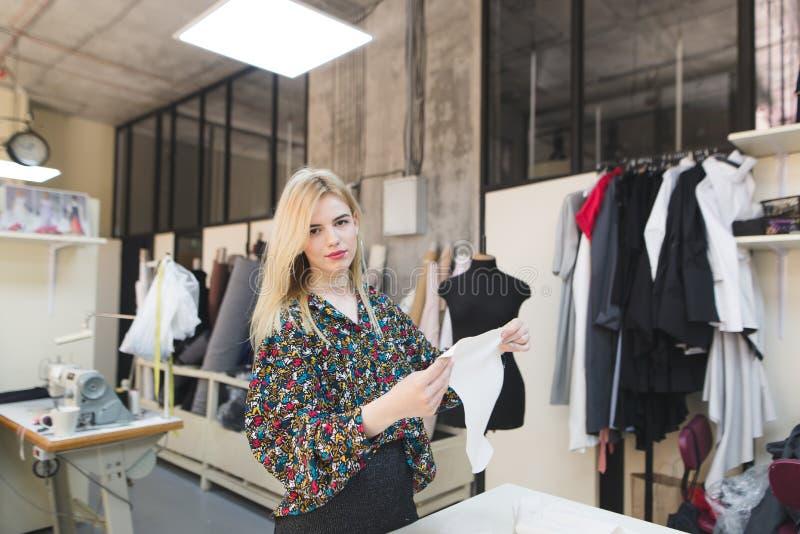La belle ouvrière couturière se tient dans un studio avec un tissu blanc dans ses mains et regards à la caméra photo stock