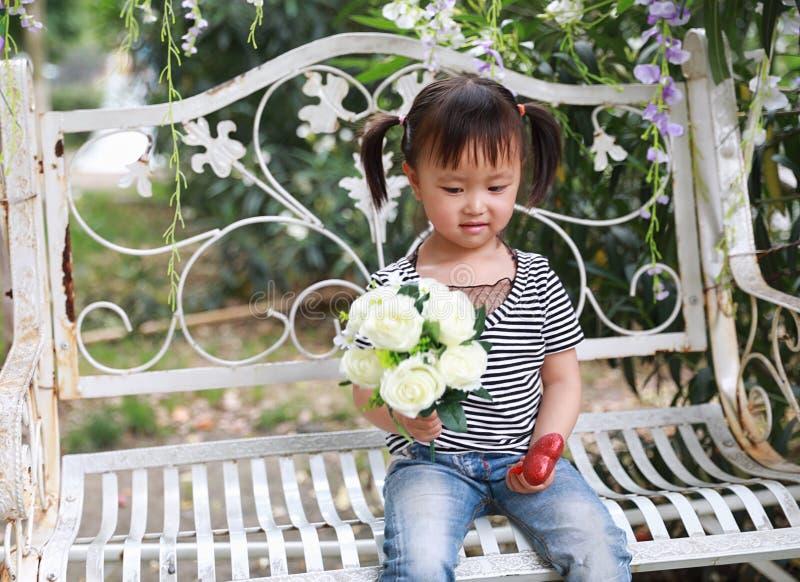 La belle petite fille adorable vilaine mignonne portent un groupe de fleurs et s'asseyent sur un banc ont l'amusement extérieur d images libres de droits