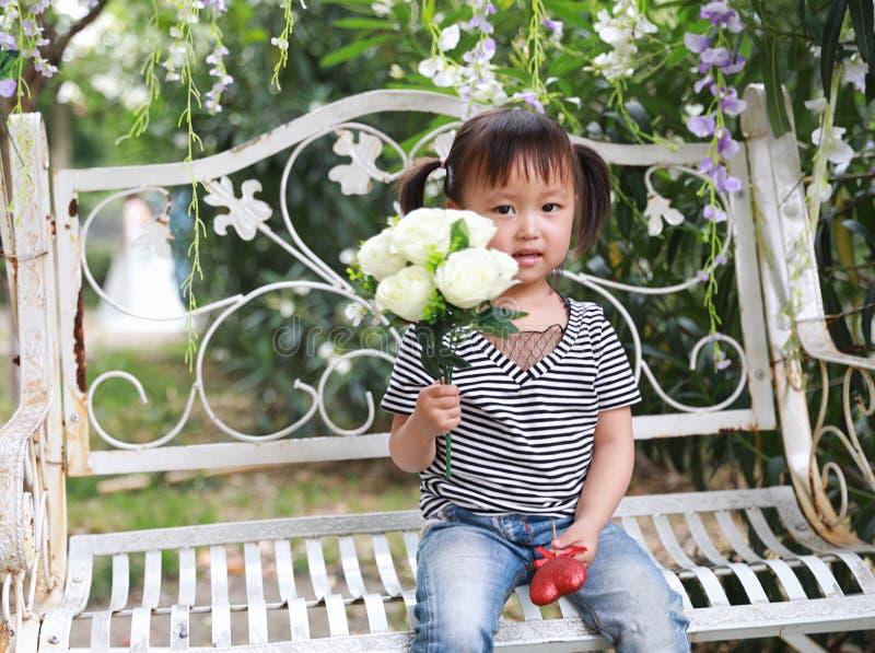 La belle petite fille adorable vilaine mignonne portent un groupe de fleurs et s'asseyent sur un banc ont l'amusement extérieur d images stock