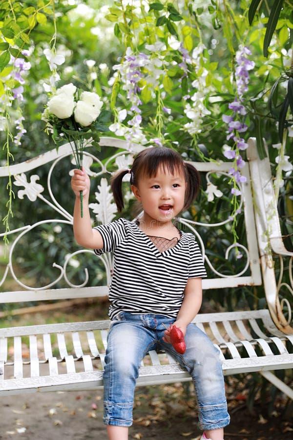 La belle petite fille adorable vilaine mignonne portent un groupe de fleurs et s'asseyent sur un banc ont l'amusement extérieur d image libre de droits