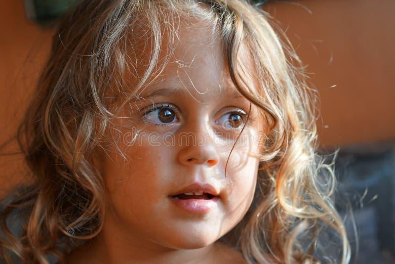 La belle petite fille blonde regarde en longueur image stock
