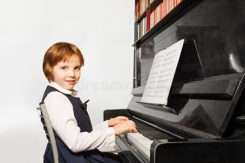 La belle petite fille dans l'uniforme scolaire joue le piano photographie stock libre de droits