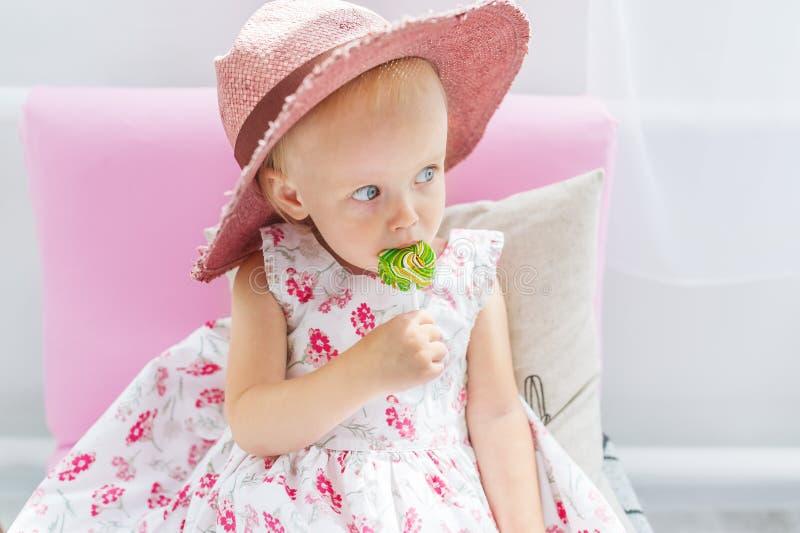 La belle petite fille dans un grand chapeau suce la lucette se reposant sur un sofa images stock